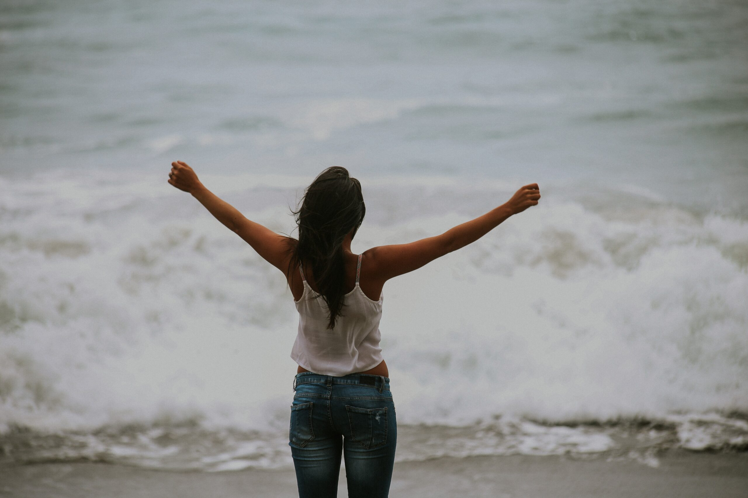 woman standing at edge of ocean with arms raised in celebration